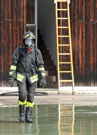 brave Fireman with the uniform wet after the fire-fighting Services tutorial