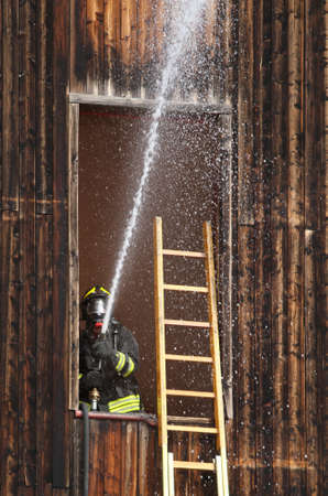 Fireman extinguish a fire with a powerful hose