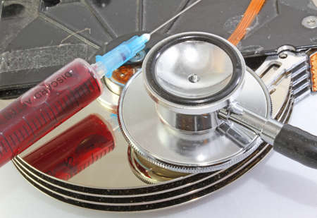 dead hard disk infected with computer virus with syringe and stethoscope photo