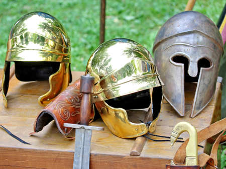 sword and helmets of ancient Roman origin and medieval helmets of brave knights and soldiers photo