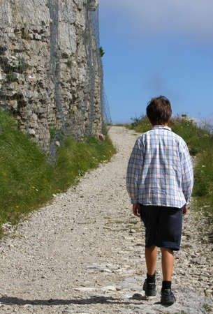 lonely child walks on the mountain path next to the huge wall of an ancient fortification of World War I built with stones
