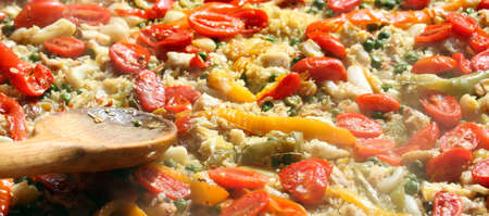 cooking Spanish paella with wooden spoon 版權商用圖片