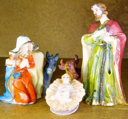characters of the crib with baby Jesus in the crib and brown background