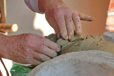 skilled: old craftsman creates a clay mask using skilled hands