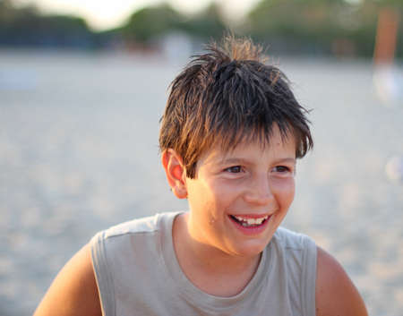 young boy smiling: Nice Italian young boy smiling in the summer at the beach