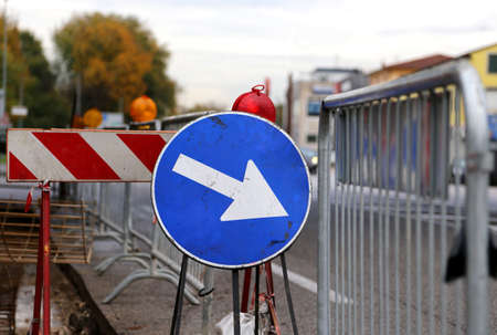 roadworks: Sign with arrow to roadworks and street excavation