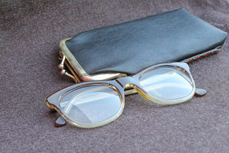 crystalline lens: glasses of an old woman with black leather case