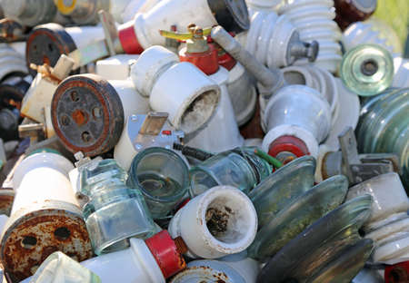 insulators: old insulators of electrical wires in glass and ceramics in a landfill Stock Photo