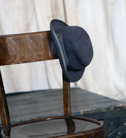old hat of an elder leaning on wooden chair Фото со стока