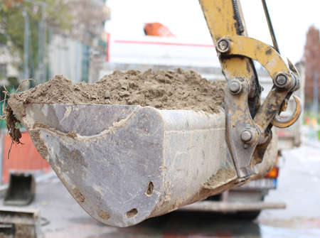 roadwork: big bucket of a bulldozer and a truck in the background Stock Photo