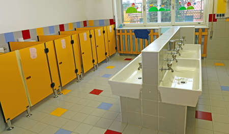 large bathroom of a nursery with white sinks, but without children Foto de archivo