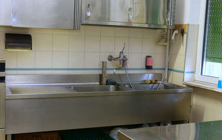 comedor escolar: Fregadero de acero y la mesa de trabajo en una cocina industrial en la cantina de la escuela Foto de archivo