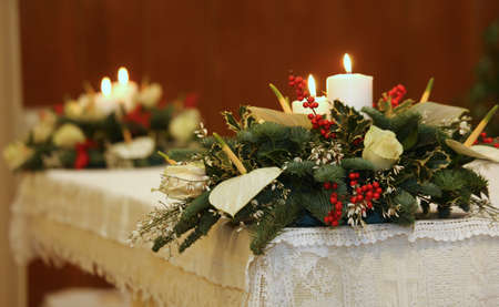 two bunches of flowers and two lit candles on the altar of the Church Foto de archivo