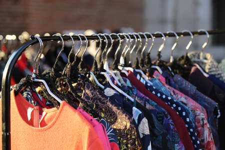 used clothes: Many vintage style clothes  for sale at an outdoor flea market