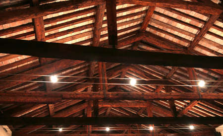 the roof with beams facing bricks and powerful halogen lamps