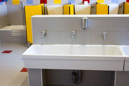 sinks: small bathrooms of a school for children with low ceramic sinks Stock Photo
