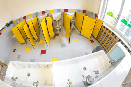 water closet: small bathroom of a school for children with water closet and sinks Stock Photo