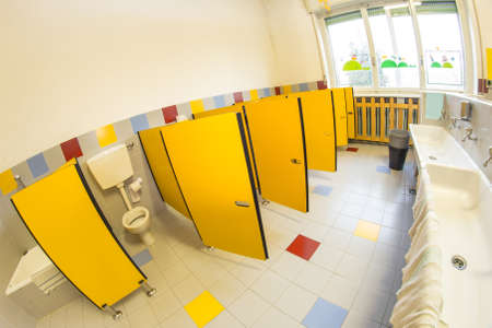 water closet: small bathroom of a school for children with water closet and white sinks Stock Photo