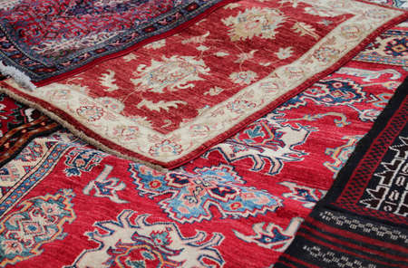 prayer rug: Red Asian rugs for sale in the shop of fabrics and textiles Stock Photo