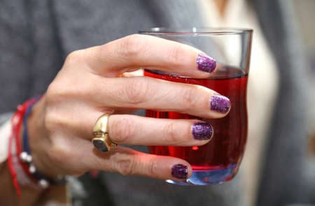 elegant womans hand that holds the glass during the apertivo