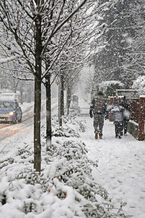 family walks in the city  sidewalk during a winter snowfall