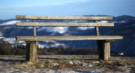 wooden bench: ancient wooden bench isolated in the high mountain landscape in winter Stock Photo