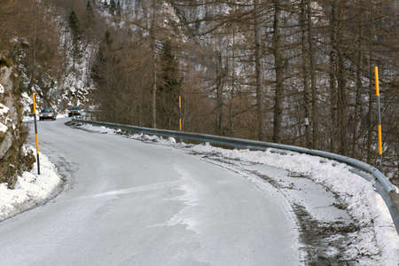 insidious: dangerous curve of a frozen mountain road in winter Stock Photo