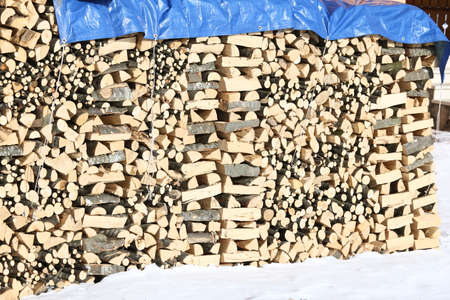 woodshed: wide Woodshed with pieces of wood piled up for the winter and white snow Stock Photo