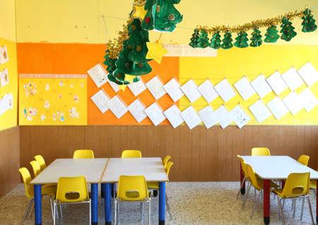 comedor escolar: aula de kindergarten con sillas amarillas y una mesa con dibujos de ni�os colgados en las paredes