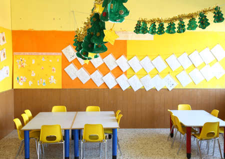 kindergarten classroom with yellow chairs and table with drawings of children hanging on the walls photo