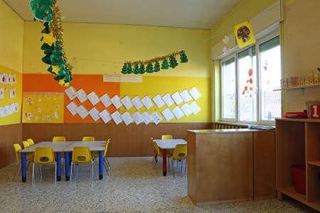 comedor escolar: Aula preescolar con sillas amarillas y una mesa con dibujos de los ni�os que cuelgan en las paredes