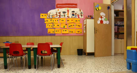 Preschool classroom with red chairs and table with drawings of children hanging on the walls