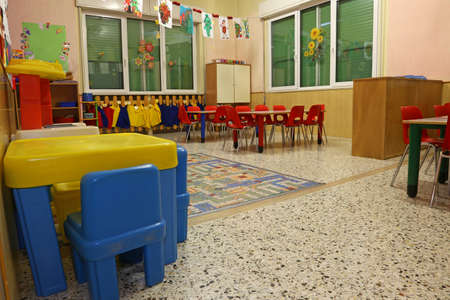 classroom: interiors of a nursery class with coloredchairs and  drawings of children hanging on the walls Stock Photo