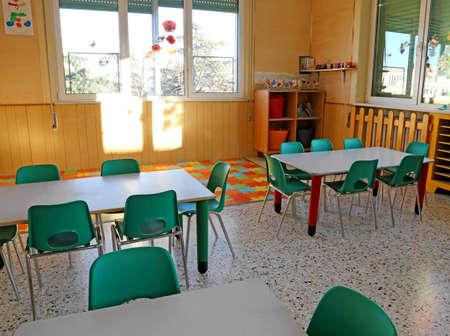 comedor escolar: interiores de una clase de jard�n de infantes con las sillas verdes y decoraciones infantiles Foto de archivo