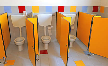 powder room: three little water closed of a kindergarten for children with yellow doors Stock Photo