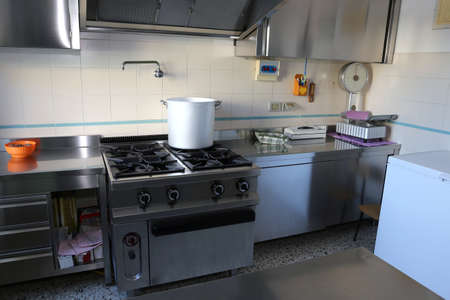 restaurateur: large industrial kitchen with big gas stove and the giant aluminum pot on the fire