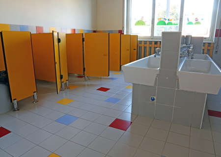 powder room: inside the bathroom of the nursery school with white ceramic sinks and doors yellow