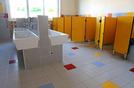 inside the bathroom of the nursery school with white sinks and doors yellow Archivio Fotografico