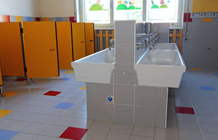 powder room: inside the bathroom of the nursery school with white sinks and doors yellow Stock Photo