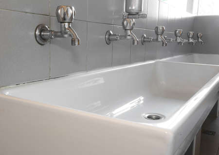 powder room: series of steel taps in white ceramic sink