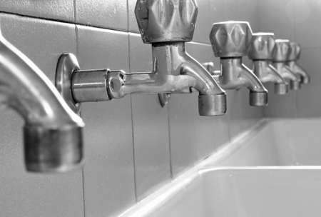 powder room: many steel taps in white ceramic sink Stock Photo