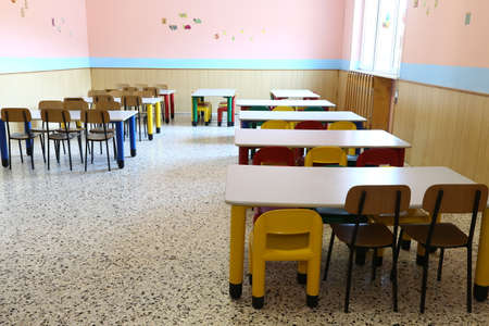 colored plastic chairs and small tables of the refectory in early