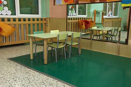 comedor escolar: mesa y sillas en la amplia sala de la guarder�a con un gran espejo en la pared