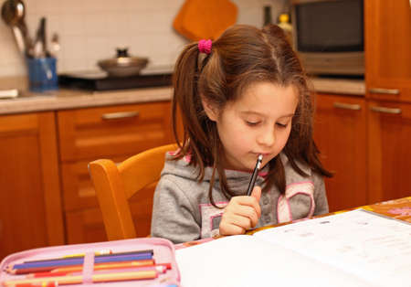 young girl writes with pencil on the school book in the kitchen photo