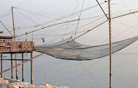 redes de pesca: enormes redes de pesca en los palafitos de madera sobre el mar