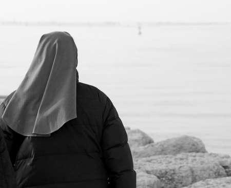 young Nun walks in winter near the sea