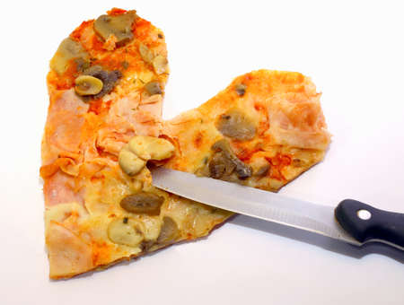 pizza in the shape of a heart with a knife in the Middle photo