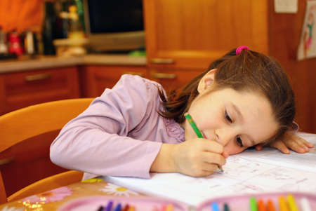 thoughtful little girl writes on her notebook 9 photo