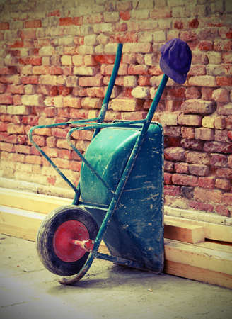 wheelbarrow: Wheelbarrow laid on the wall and workers Cap Stock Photo