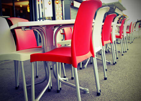 Red and white chairs with tables in an outdoor bar Stock fotó